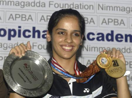 India's badminton player Saina Nehwal holds her medals from the Singapore Open Series, India Open Grand Prix and Djarum Indonesia Open Super Series tournaments during a news conference in Hyderabad June 29, 2010. REUTERS/Krishnendu Halder/Files