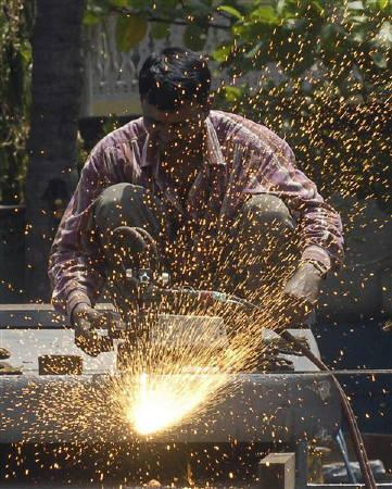 An employee works inside a steel factory in Hyderabad June 3, 2010. REUTERS/Krishnendu Halder/Files