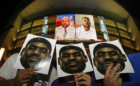 Miami Heat fans hold images of the NBA star LeBron James after he announced his free agency plans outside the American Airlines Arena in Miami July 8, 2010. REUTERS/Hans Deryk
