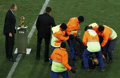 <p>Policiais removem homem que invadiu o gramado do estádio Soccer City após ele cobrir a taça da Copa do Mundo com um boné antes da final entre Holanda e Espanha. Em Johanesburgo, 11 de julho de 2010. REUTERS/David Gray</p>
