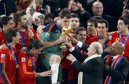 FIFA President Sepp Blatter (2nd R) and South African President Jacob Zuma (R) hand the World Cup trophy to Spain's team captain Iker Casillas (C) during the award ceremony at Soccer City stadium in Johannesburg July 11, 2010.  REUTERS/Michael Kooren