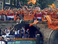 <p>Torcedores realizam desfile nos canais de Amsterdã para recepcionar os jogadores da seleção holandesa de futebol. REUTERS/United Photos/Robin van Lonkhuijsen</p>