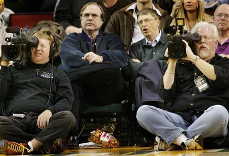 Microsoft co-founders Bill Gates and Paul Allen watch an NBA game at Key Arena in Seattle, January 5, 2004. REUTERS/Anthony P. Bolante