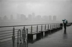 <p>A pedestrian walks in the rain along the waterfront with the New Jersey skyline in the background, in New York April 15, 2007. REUTERS/Eric Thayer</p>
