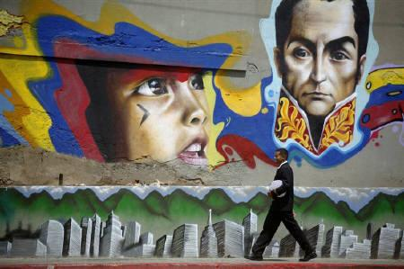 A soldier walks past a wall with graffiti of South American hero Simon Bolivar on the 200th anniversary of Venezuela's independence in Caracas April 19, 2010. Venezuela exhumed the remains of 19th century independence hero Simon Bolivar on Friday and will test them to see if he was poisoned by enemies in Colombia. REUTERS/Gil Montano