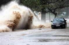 <p>A car drives past a wave caused by Typhoon Conson in Vietnam's northern Hai Phong city July 17, 2010. REUTERS/VNA</p>