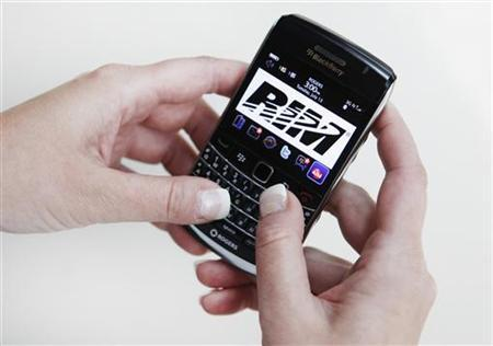A person poses while using a Blackberry Bold 2 smartphone made by Research in Motion (RIM), July 13, 2010. The company will hold its annual general meeting of shareholders today. REUTERS/Mark Blinch