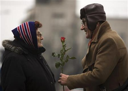 A man offers a rose to a woman to mark International Women's Day in Belgrade March 8, 2010. REUTERS/Marko Djurica