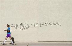 "<p>A man walks past graffiti on a building reading ""Smash The Border"" in Phoenix, Arizona April 29, 2010. REUTERS/Joshua Lott</p>"