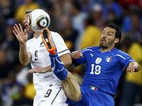 <p>Gianluca Zambrotta da Itália disputa a bola com o neozelandês Shane Smeltz (esq) durante jogo pelo Grupo F da Copa do Mundo. O lateral da seleção italiana renovou seu contrato com o Milan nesta quinta-feira. 20/06/2010 REUTERS/Jerry Lampen/Arquivo</p>