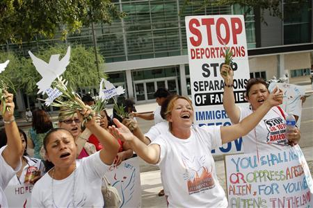 Maria Uribe (C) and Giorgina Sanches (L) sing with other demonstrators as they protest against Arizona's controversial immigration law outside the U.S. District Court in Phoenix July 22, 2010. REUTERS/Joshua Lott