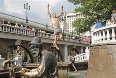 <p>A man jumps into a fountain to cool down in central Moscow July 20, 2010. Temperatures reached 31 degrees Celsius (87.8 degrees Fahrenheit) in the Russian capital on Monday. REUTERS/Denis Sinyakov</p>