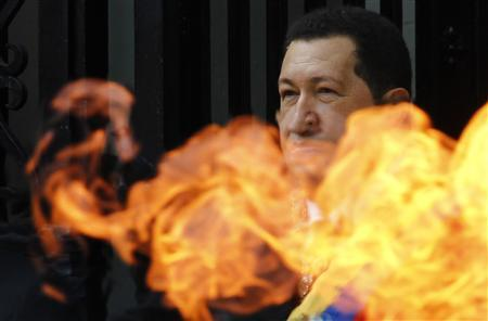 Venezuelan President Hugo Chavez greets supporters as he stands behind a flame from the torch at the entrance of Simon Bolivar's tomb in Caracas July 24, 2010, Chavez is attending a ceremony to mark the birthday of independence hero Bolivar at Caracas' national cemetery. REUTERS/Jorge Silva