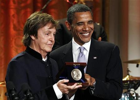 President Barack Obama smiles next to Paul McCartney at the White House in Washington June 2, 2010. REUTERS/Kevin Lamarque