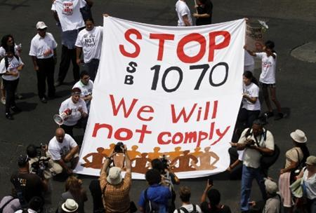 Demonstrators hold a banner as they protest against Arizona's controversial Senate Bill 1070 immigration law outside the U.S. District Court in Phoenix July 22, 2010. REUTERS/Joshua Lott