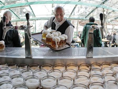 A waiter takes a tablet of beer mugs on the opening day of Schweizerhaus beer garden in Vienna March 15, 2010. REUTERS/Heinz-Peter Bader