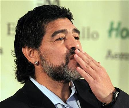 Former Argentina's national soccer team coach Diego Maradona blows kisses as he arrives to read a statement in Buenos Aires July 28, 2010. REUTERS/Enrique Marcarian