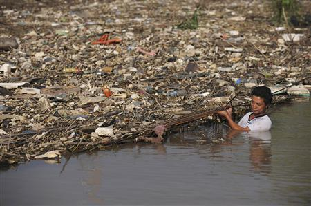 A worker clears floating garbage washed down by recent torrential rain on the Yangtze River in Wuhu, Anhui province, August 2, 2010. REUTERS/Stringer