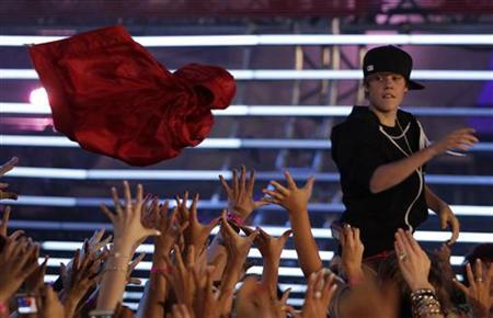Singer Justin Bieber throws his coat into the crowd as he performs at the 2010 MuchMusic Video Awards in Toronto June 20, 2010. REUTERS/Mike Cassese