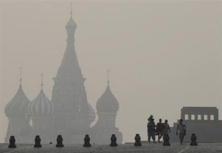 People walk along Moscow's Red Square with St. Basil's Cathedral and the mausoleum of Soviet state founder Vladimir Lenin seen in the background through heavy smog caused by peat fires in nearby forests, August 2, 2010. REUTERS/Alexander Natruskin
