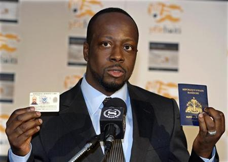 Grammy Award-winning musician Wyclef Jean, a native of Haiti, holds up his U.S. ''Green Card'' and his Haitian passport as he recounts his experiences after returning from Haiti at a news conference in New York, January 18, 2010. REUTERS/Ray Stubblebine