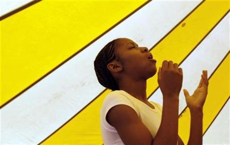 Shavon Gardner, 17, prays as she sings with the Redeemed Christian Church of God youth choir at Redemption Camp in Floyd, Texas June 17, 2009. REUTERS/Jessica Rinaldi