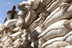 <p>An unidentified government official sits on sacks of wheat donated by the U.S. at a food distribution point near Jijiga, eastern Ethiopia December 1, 2009. REUTERS/Barry Malone</p>