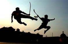 <p>Students practise sword-fighting at a kung fu school in Hefei, east China's Anhui province August 9, 2006. REUTERS/Jianan Yu</p>