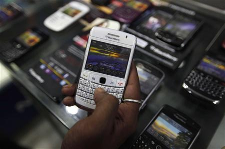 A customer holds a BlackBerry handset inside a mobile selling shop in Kolkata August 12, 2010. REUTERS/Rupak De Chowdhuri