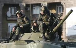 <p>Солдаты сидят на танке, блокируя дорогу в центре Еревана, 2 марта 2008 года. Срок пребывания российских военных в Армении будет продлен до 2044 года, что будет способствовать усилению позиций Москвы в стратегически важном регионе Закавказья. REUTERS/David Mdzinarishvili</p>