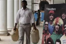 <p>A man carries empty water containers as he walks past a Blackberry billboard in New Delhi August 12, 2010. REUTERS/Adnan Abidi</p>