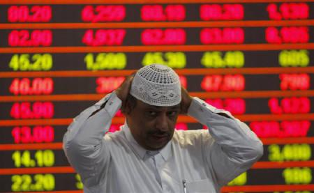 An investor monitors market activity at Doha Securities Market December 6, 2009. REUTERS/ Fadi Al-Assaad/Files