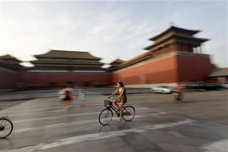 A foreign visitor rides a bicycle past Wumen Gate at the Forbidden City in Beijing August 1, 2010. REUTERS/Jason Lee
