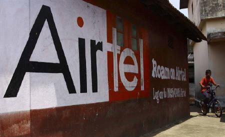 A boy rides his bicycle past an advertisement of Bharti Airtel in Kochi in this March 31, 2010 file photo. Bharti Airtel has won the rights to sponsor all cricket series played in India until 2013. REUTERS/Sivaram V