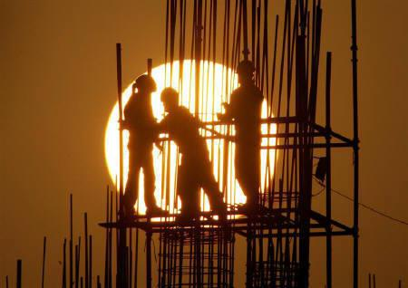 Labourers are silhouetted by the sun during sunset at a construction site in New Delhi December 31, 2005. The initial response to IFCI's infrastructure bonds has been good, a company official said, with additional tax-saving incentive making them an attractive option for investors. REUTERS/B Mathur/Files