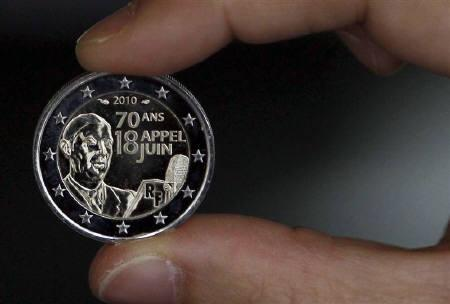 An employee displays a new 2 Euro coin which commemorates the 70th anniversary of General Charles de Gaulle's in Pessac, south western France, June 17, 2010.  REUTERS/Regis Duvignau/Files