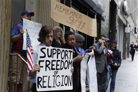 Demonstrators who support and oppose a proposed Muslim cultural center and mosque Park51 stand with signs in front of the site in New York August 25, 2010. REUTERS/Lucas Jackson