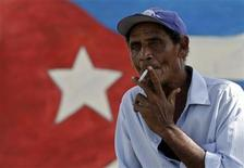 <p>A man smokes a cigarette near a mural with a Cuban flag in Holguin August 21, 2010.REUTERS/Enrique De La Osa</p>