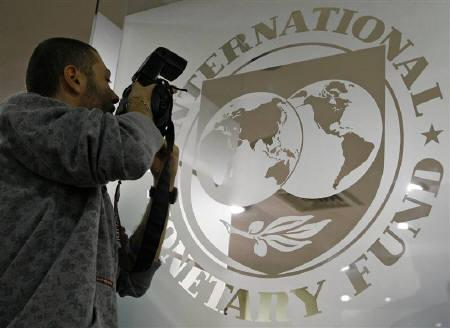 A photographer takes pictures through a glass carrying the International Monetary Fund (IMF) logo during a news conference in Bucharest March 25, 2009. REUTERS/Bogdan Cristel/Files