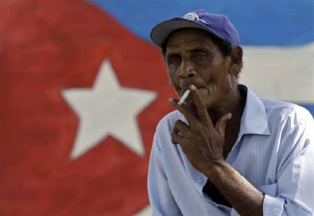 8月25日、キューバ政府が、長年続けてきたたばこの配給を9月から停止すると発表した。写真はオルギンでたばこを吸う男性。21日撮影(2010年 ロイター/Enrique De La Osa)