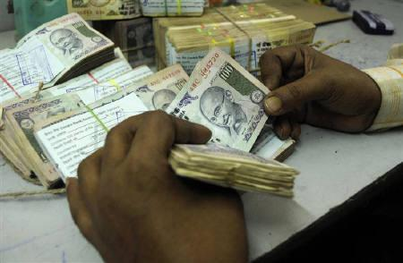 An employee counts currency notes at a cash counter inside a bank in Agartala, capital of Tripura, January 29, 2010. REUTERS/Jayanta Dey/Files