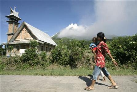 A woman carrying her child walks on the street at the district of Tanah Karo outside the city of Medan, North Sumatra, as Mount Sinabung volcano spews smoke in the background August 28, 2010. REUTERS/Tarmizy Harva