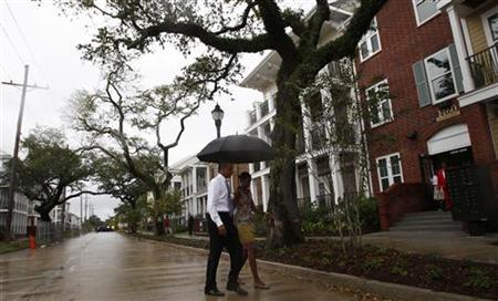 President Barack Obama and first lady Michelle Obama cross the street in the Columbia Parc Development to visit newly built homes in New Orleans, Louisiana, August 29, 2010. REUTERS/Jim Young