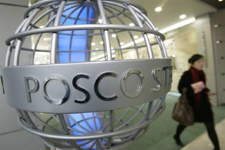 A woman walks past a sculpture of POSCO's logo at its headquarters in Seoul February 2, 2007. REUTERS/You Sung-Ho/Files