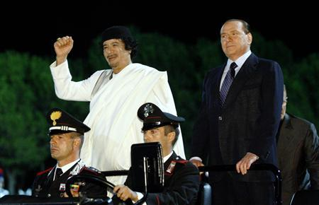 Italy's Prime Minister Silvio Berlusconi (R) and Libyan leader Muammar Gaddafi arrive to attend a carousel performed by Italian Carabinieri Cavalry and Barbary Cavalry in Rome August 30, 2010. REUTERS/Remo Casilli