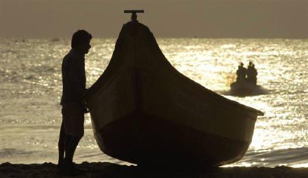 A fisherman stands next to a boat before heading into sea to catch fish on the Marina beach in Chennai in this September 18, 2009 file photo. India expressed concerns about China's influence in Indian Ocean region, the latest sign of tension between the Asian giants who are competing for  geopolitical power in the region. REUTERS/Babu/Files