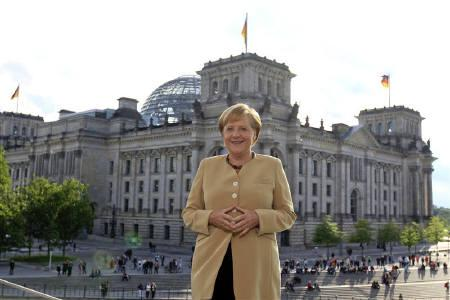 German Chancellor Angela Merkel poses for photographers after the television recording of her summer interview in front of the Reichstag, the seat of the German lower house of parliament Bundestag, in Berlin, August 29, 2010. REUTERS/Michael Dalder/Files