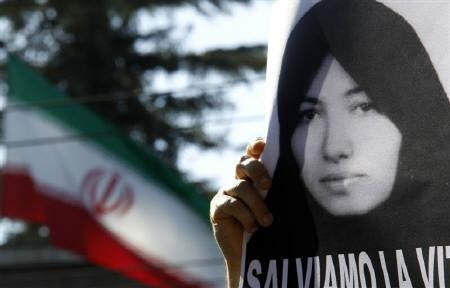 A demonstrator holds a picture of Sakineh Mohammadi Ashtiani, in front of the Iranian Embassy in Rome September 2, 2010. REUTERS/Stefano Rellandini