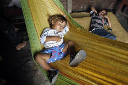 A child sleeps in a hammock, as his parents collect recyclable materials from Managua's municipal garbage dump, July 23, 2010. REUTERS/Oswaldo Rivas