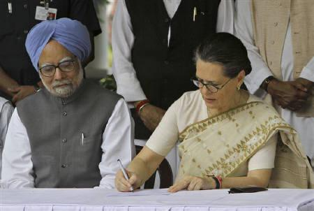 Congress party president Sonia Gandhi watched by Prime Minister Manmohan Singh fills nomination papers seeking to retain her post as the party chief at her residence in New Delhi September 2, 2010. REUTERS/B Mathur